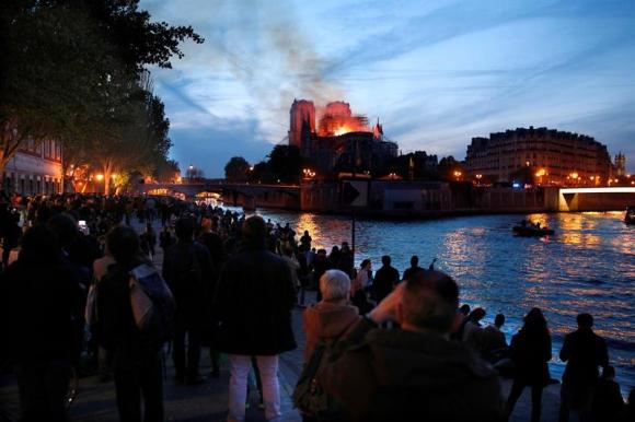 Decenas de personas en la orilla del río Sena observan la columna de humo y las llamas que consumen a la catedral de Notre Dame. Foto: EFE.