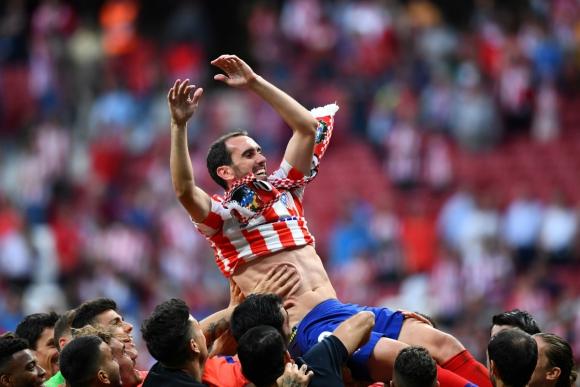 Godín llevado en andas por sus compañeros en su último partido en el Wanda Metropolitano. Foto: AFP.