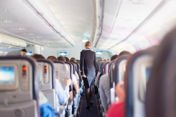 Azafata en pasillo de un avión y viajeros