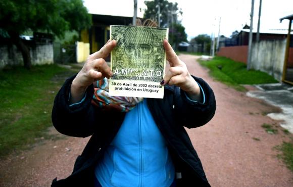 Vecina de cooperativa de Casavalle muestra cartel de amianto. Foto: Fernando Ponzetto