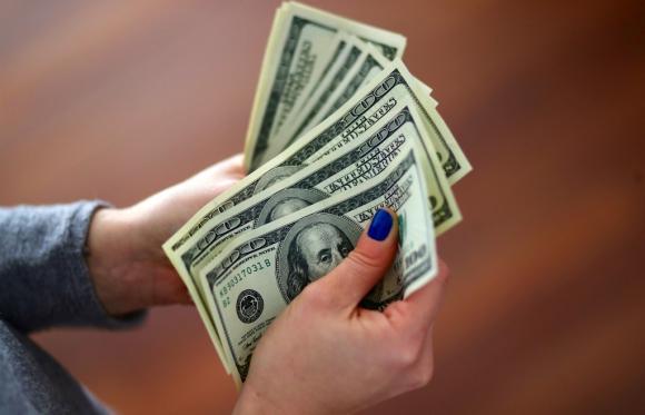 Mujer contando dólares. Foto: Reuters