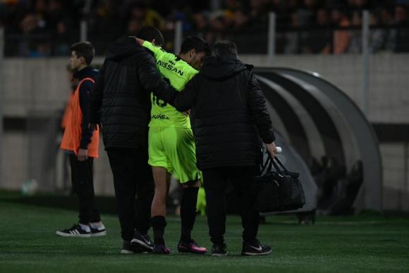 Agustín Canobbio saliendo del campo de juego ayudado tras la lesión. Foto: Gerardo Pérez.