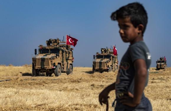 Vehículos militares turcos, parte de un convoy militar estadounidense, participan en una patrulla conjunta en la aldea siria de al-Hashisha en las afueras de la ciudad de Tal Abyad a lo largo de la frontera con Turquía. Foto: AFP