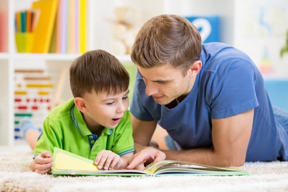 Niño y padre leen un libro. Foto: Shutterstock.