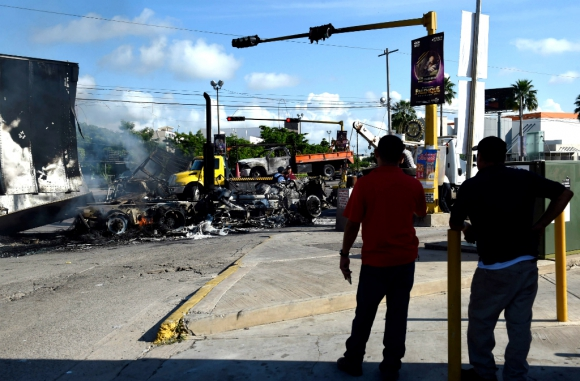 Dos habitantes de Cualiacán observan el panorama con vehículos quemados en los tiroteos entre narcos y militares. Foto: AFP