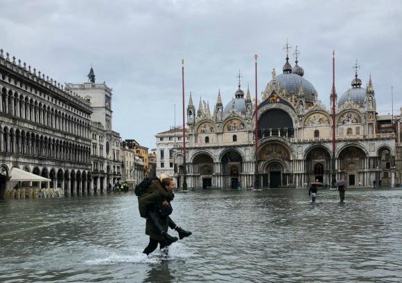 Una persona carga a otra en la Plaza San Marcos inundada. Foto: Reuters