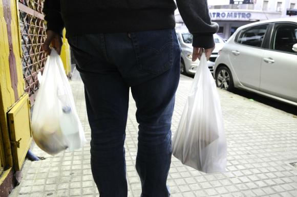 Hombre lleva en bolsa de plástico productos comprados en un supermercado. Foto: Darwin Borrelli