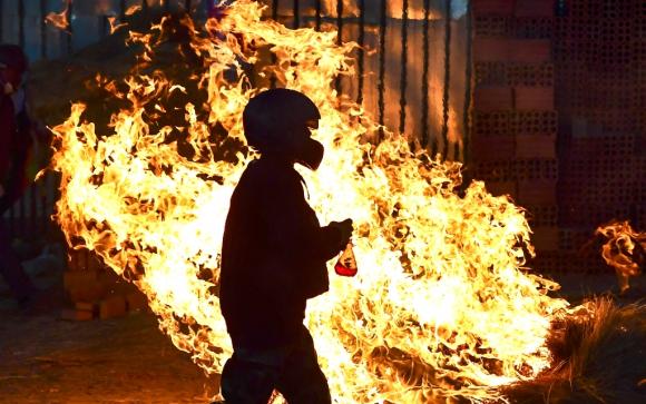 Un partidario de Evo Morales pasa cerca de una barricada en llamas, en las protestas realizadas en la provincia de Chapare. Foto: AFP