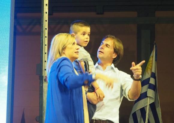 En pleno discurso de Beatriz Argimón un niño se separó de sus padres y Luis Lacalle bajó del tablado para subirlo con ellos. Foto: Ricardo Figueredo
