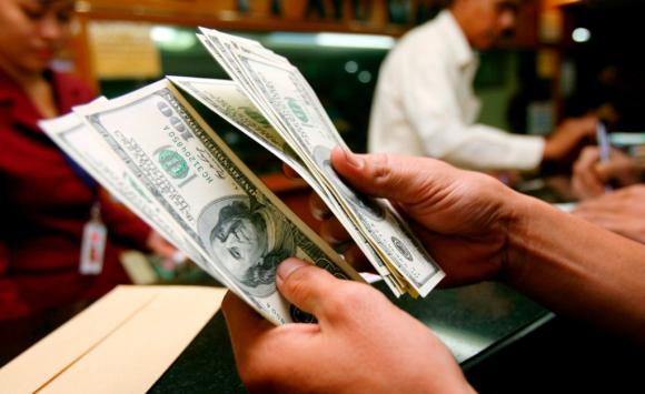 Persona contando dólares en una casa de cambio. Foto: Archivo El País