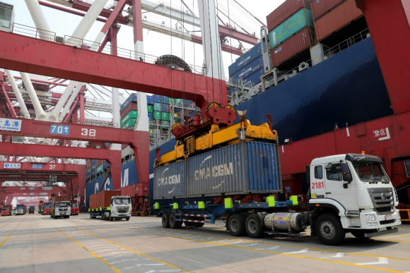 Camión descarga un contenedor en un puerto de China. Foto: EFE