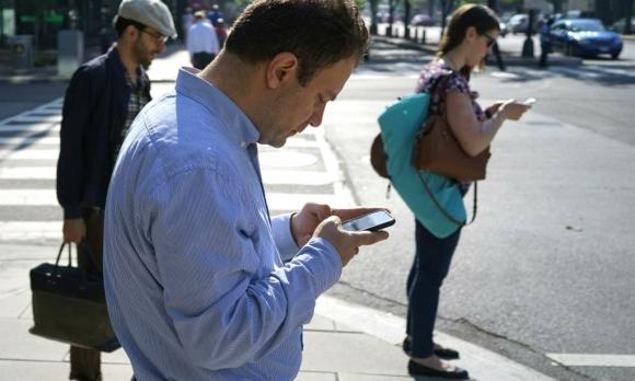 Personas mirando el celular en la calle. Foto: AFP