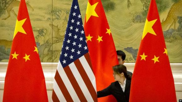 Funcionarios preparan banderas de EE.UU. y China previo a una conferencia. Foto: Archivo El País