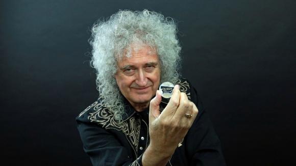 El guitarrista Brian May de la banda Queen posa con una moneda de 5 libras. Foto: Reuters.