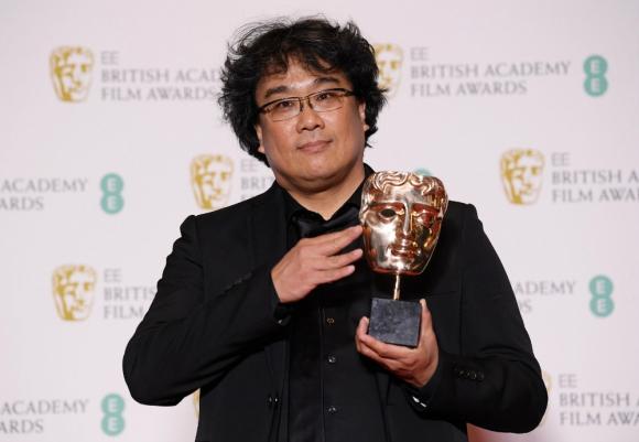 Bong Joon Ho con el Bafta a mejor guion original. Foto: AFP