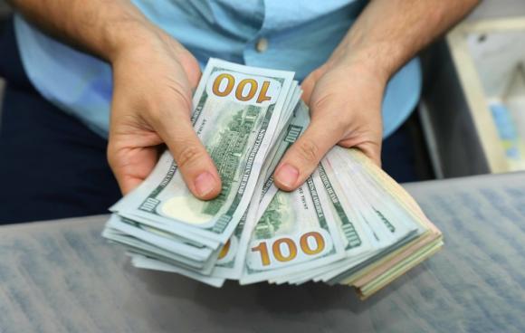 Un hombre cuenta dólares en una casa de cambio de moneda. Foto: AFP
