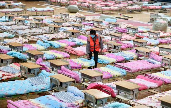 Trabajador instala camas en un estadio Hongshan para convertirlo en un hospital improvisado tras brote de coronavirus, Foto: Reuters