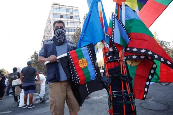 Un vendedor ambulante ofrece banderas mapuche durante una protesta en Chile. Foto: EFE.