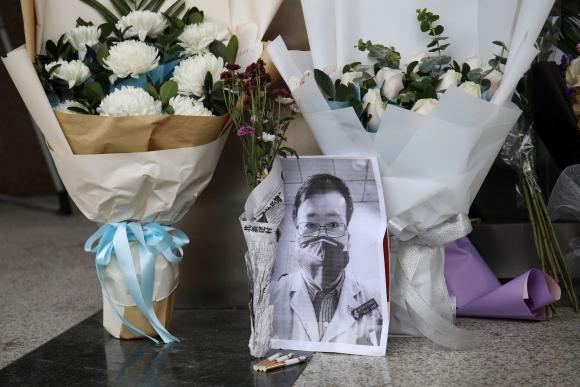 La foto del Dr. Li Wenliang y ofrendas florales en recuerdo del oftalmólogo, en un ala del Hospital Central de Wuhan. Foto: Reuters.