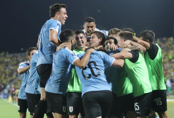 El plantel de Uruguay y la celebración de uno de los goles ante Colombia en el Sub 23. Foto: Reuters.