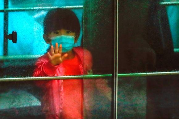 Un niño con tapabocas saluda mientras es evacuado de un edificio en el marco de la lucha contra el coronavirus. Foto: Reuters