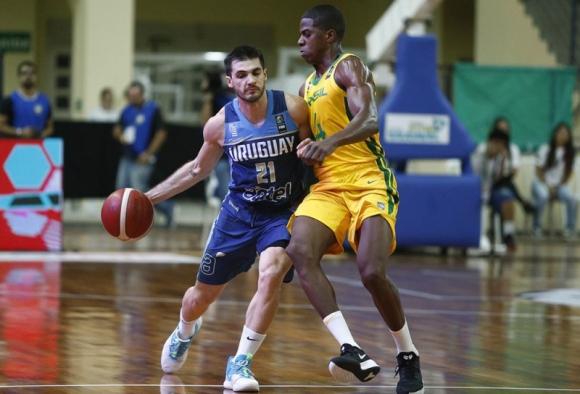 Luciano Parodi ante George de Paula en el duelo entre Uruguay y Brasil por Eliminatorias de Americup. Foto: FIBA.