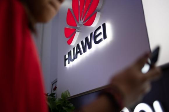 Silueta de una persona sostiene un teléfono Huawei. Foto: AFP