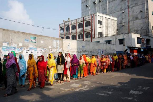 Trabajadoras de la industria textil usan máscaras faciales protectoras mientras hacen cola antes de ingresar a una fábrica en Bangladesh. Foto: EFE.