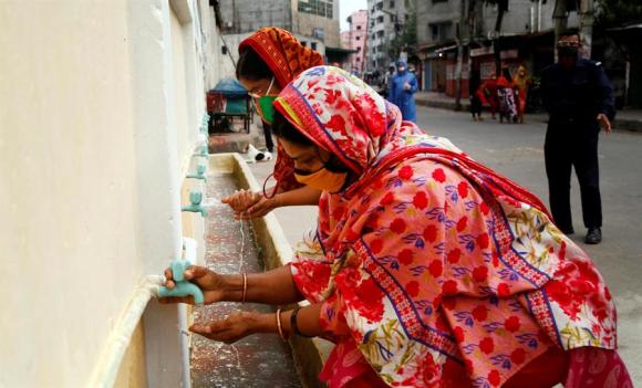 Trabajadoras se lavan las manos antes de ingresar a una fábrica después de la reapertura de estas a escala limitada. Foto: EFE.
