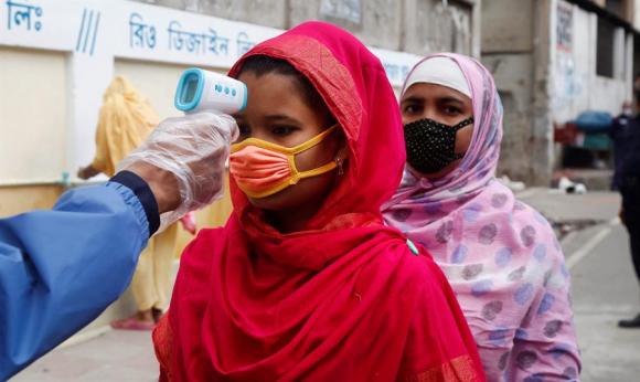 Un funcionario de la fábrica de prendas de vestir verifica la temperatura corporal de una trabajadora. Foto: EFE.