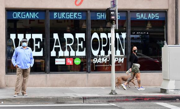 Peatones usan barbijo frente a un restaurante en Los Ángeles, California. Foto: AFP.
