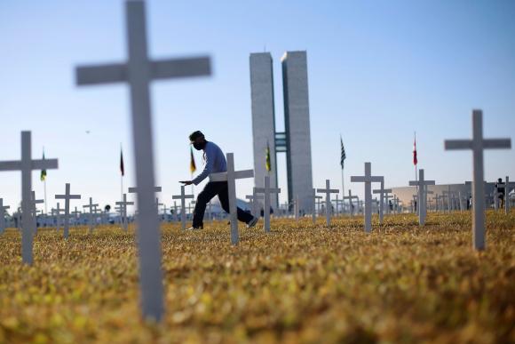 Mil cruces clavadas frente al Congreso brasileño como parte de una manifestación recordaron ayer las más de 57.000 víctimas que el coronavirus ha dejado en Brasil. Foto: Reuters