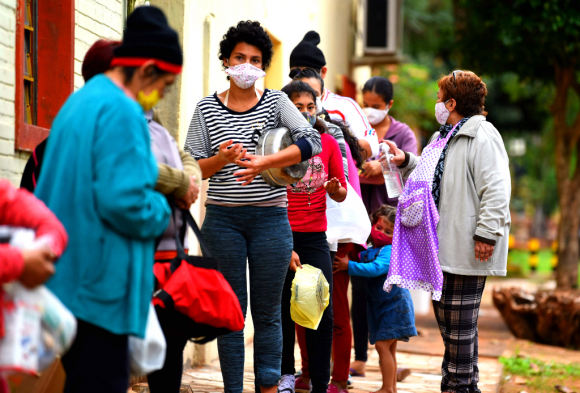 Fila de personas utilizando tapaboca en América Latina. Foto: AFP
