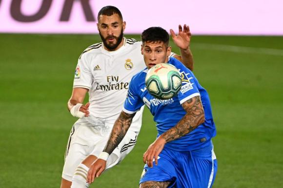 Mathías Olivera y Karim Benzema disputan la pelota en el Real Madrid-Getafe. Foto: AFP.