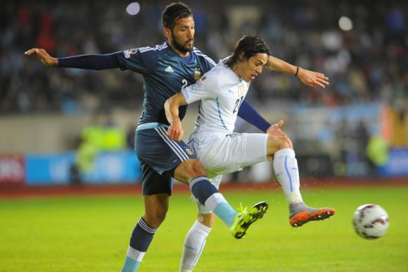 El argentino Ezequiel Garay y Edinson Cavani en un duelo entre Argentina y Uruguay. Foto: Archivo El País.