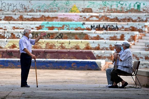 Ancianos españoles charlan en una plaza del barrio de Vallecas en Madrid en septiembre. Foto: AFP.