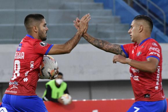 Melgar y Orfano celebran uno de los goles de Jorge Wilstermann ante Peñarol. Foto: AFP.
