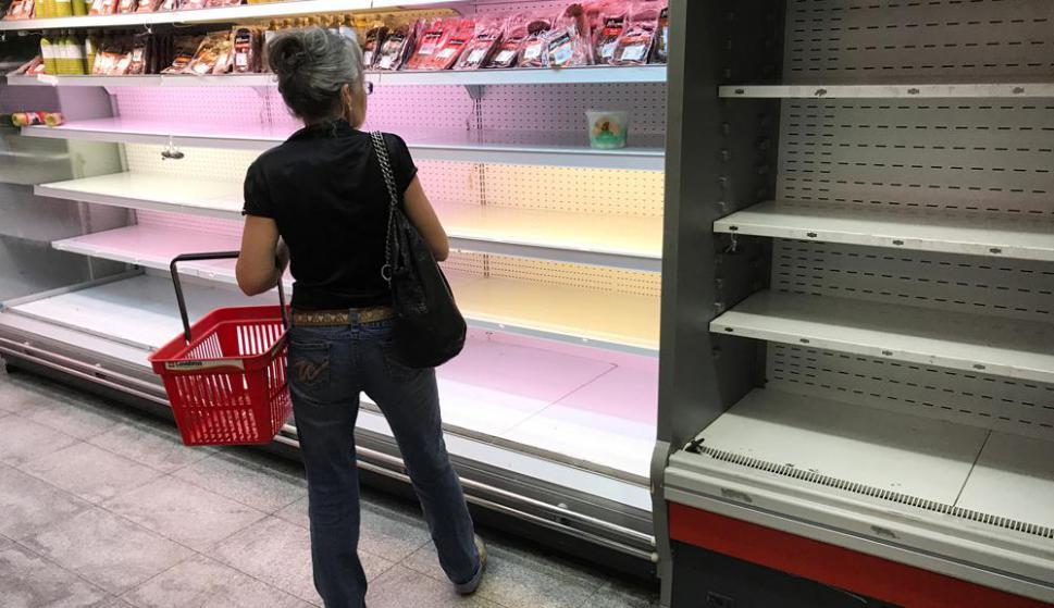 Una mujer mira precios en un supermercado de Caracas que refleja la gran escasez de alimentos que sufre el país. Foto Reuters
