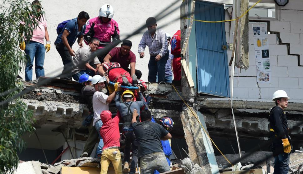 Rescatistas trabajan arduamente para ayudar a las personas atrapadas. Foto: AFP
