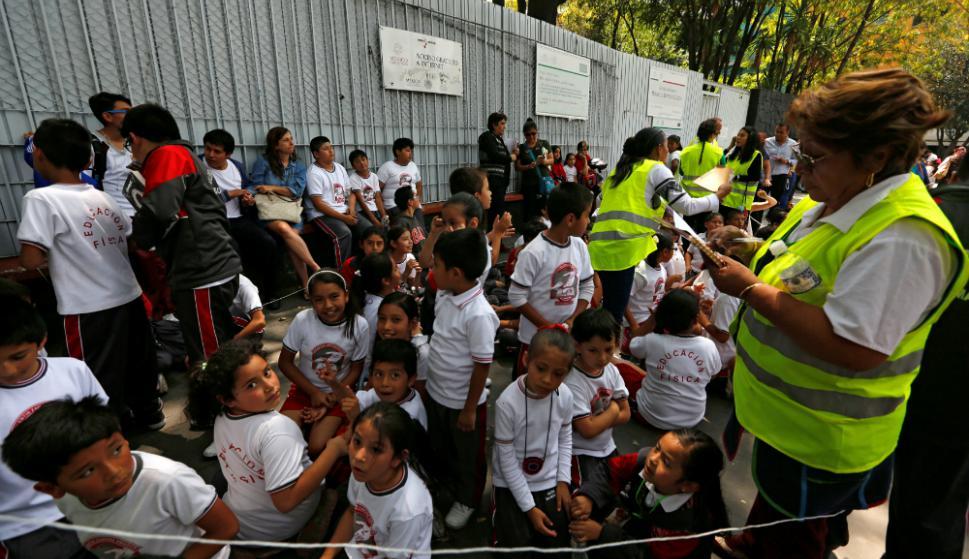 Niños esperan resguardados y se protegen de los escombros. Foto: Reuters