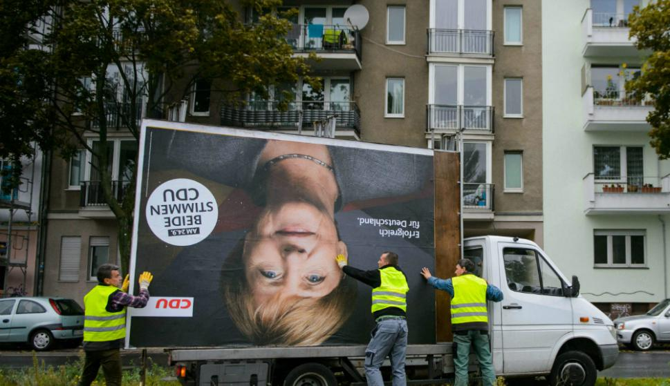 Empleados de una empresa publicitaria retiran una cartelera con la imagen de Merkel. Foto. AFP