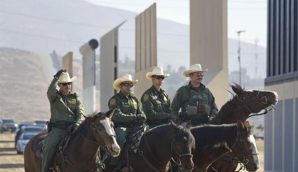 Policías frente a los prototipos de muro. Foto: EFE