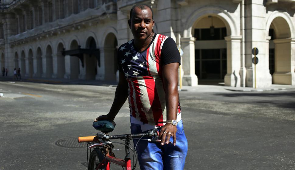 Un cubano con una camiseta de EE.UU. camina con su bicicleta por La Habana. Foto: EFE