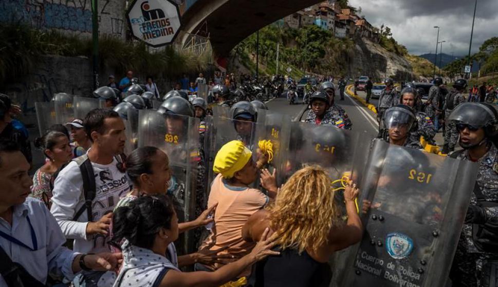 Un grupo de personas protesta frente a miembros de la Policía Nacional Bolivariana. Foto: EFE
