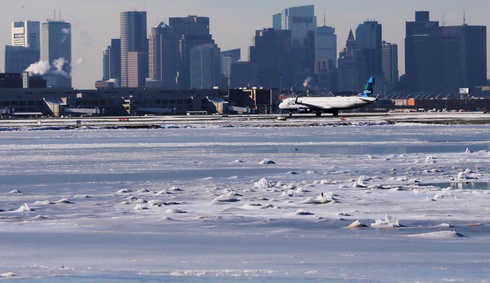 Un avión  espera para despegar junto a las aguas congeladas del puerto. Foto: Reuters