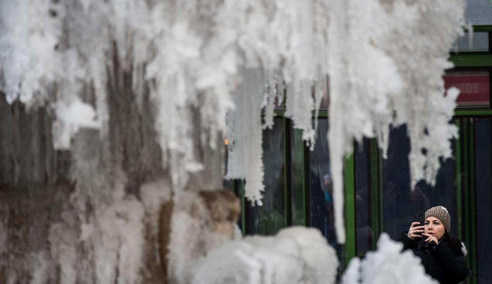 Una mujer retrata el agua congelada de una fuente. Foto: AFP
