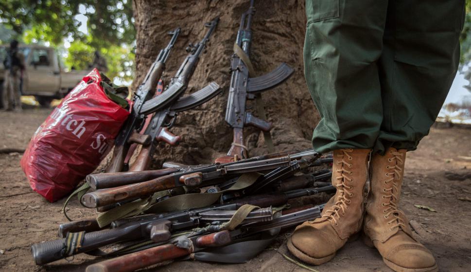 Un joven se para junto a las armas de los soldados liberados. Foto: AFP