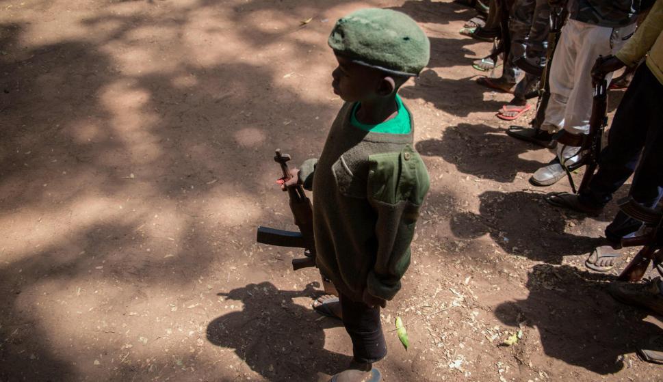 Joven se mantiene de pie con su arma en la ceremonia de liberación. Foto: AFP