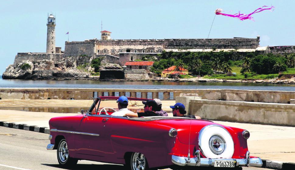 Paseo. Turistas recorren el Malecón de La Habana en uno de los autos antiguos que se ven todos los días en las calles de la capital. Foto: EFE