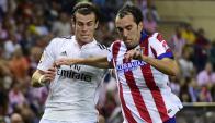 Clásico. Bale y Godín en un duelo que se va a repetir. Foto: AFP